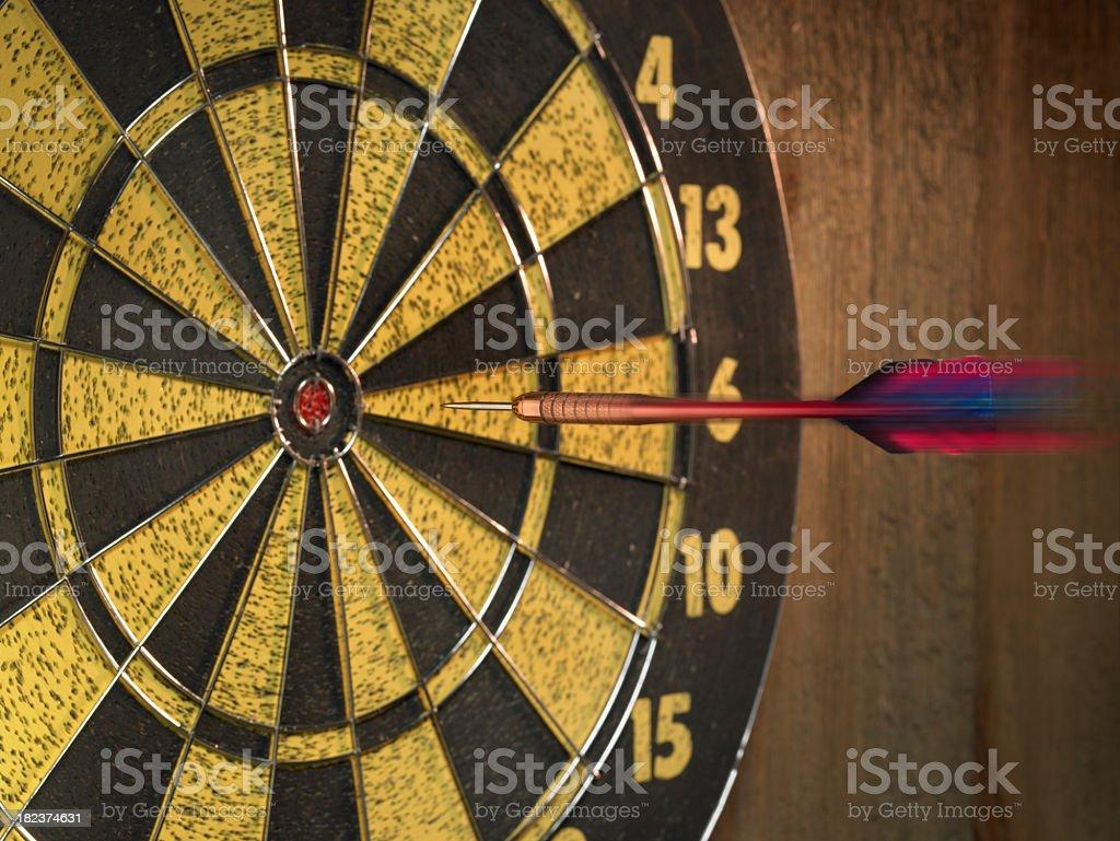 Close-up of dart flying towards bulls-eye of dartboard royalty-free stock photo