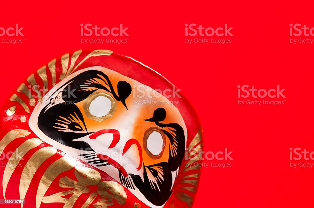 close-up of daruma doll on red background stock photo
