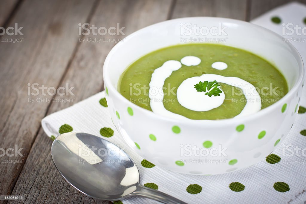 Close-up of decorated pea soup in a green dots napkin stock photo