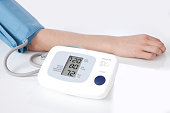 Close-up of digital blood pressure meter attached to arm