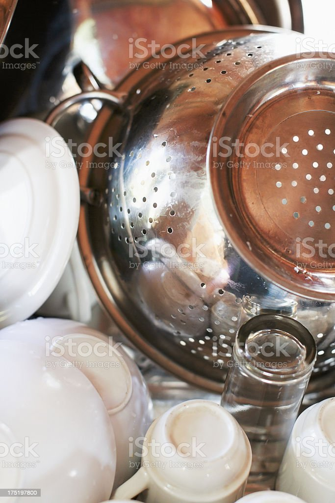 Close-up of dishes and colander stacked in drying rack stock photo