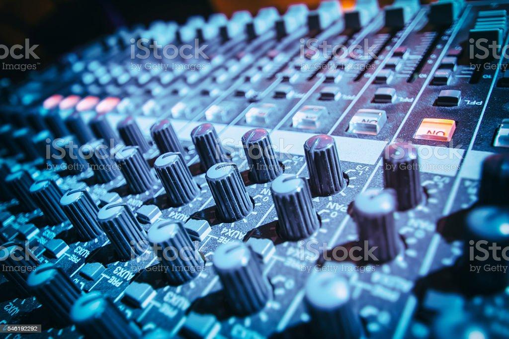 Close-up of DJ's sound mixing desk illuminated by blue light stock photo