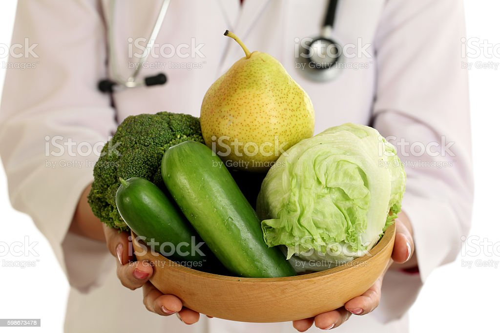 Closeup of doctor holding a bowl of vegetables against white background stock photo