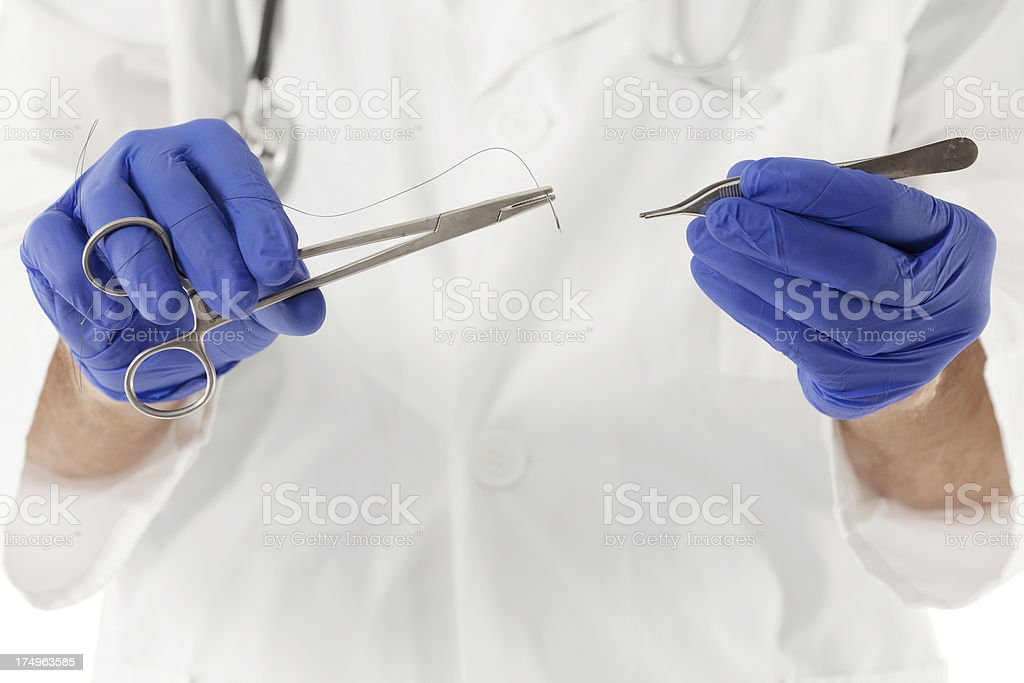 Close-up of doctor's hands with surgical instruments stock photo