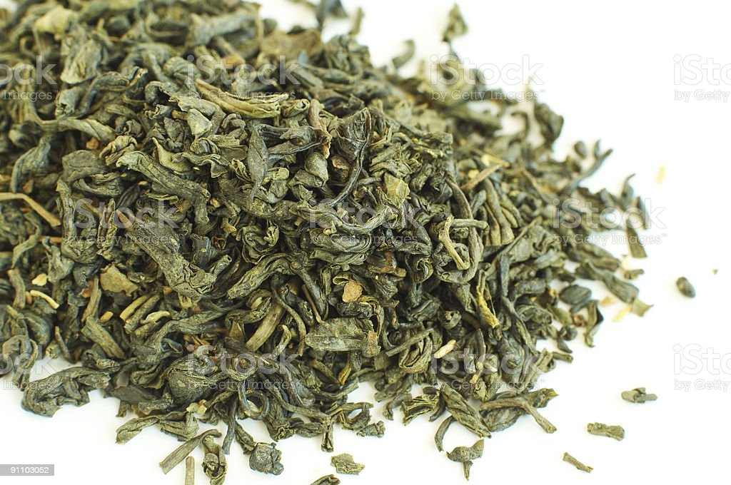 Close-up of dry green tea on white background stock photo