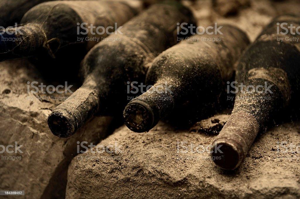 Close-up of dusty black wine bottles on gray rocks stock photo