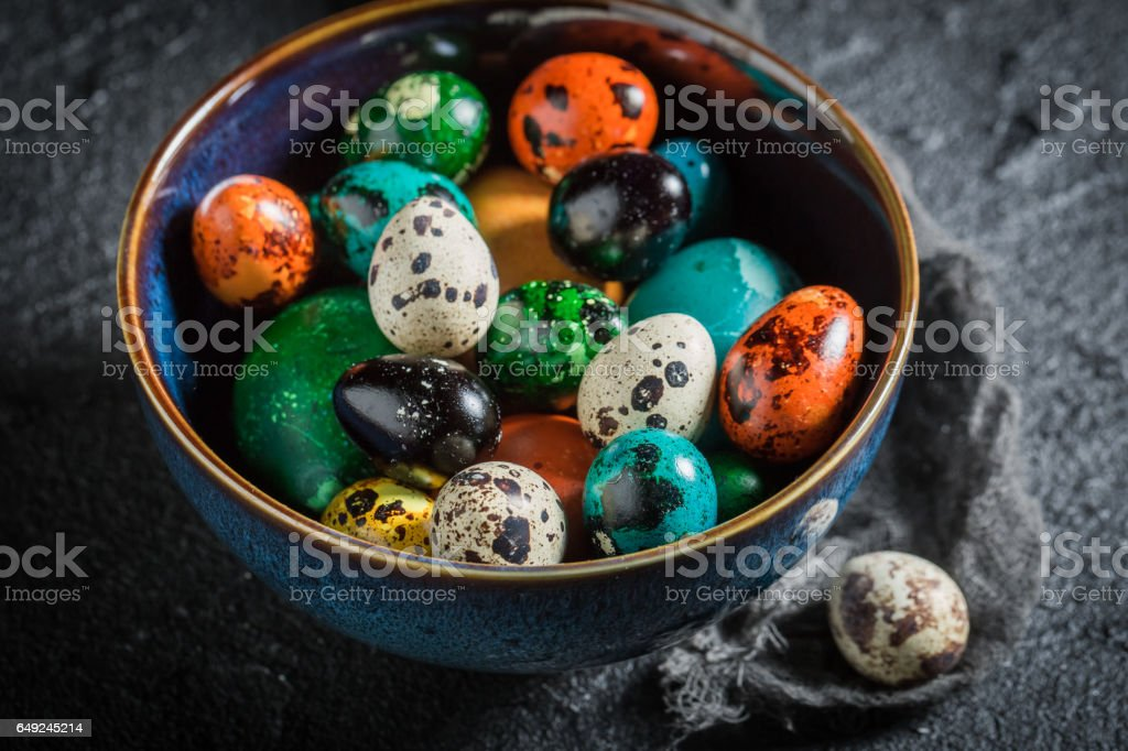 Closeup of Easter eggs in blue bowl on black rock stock photo