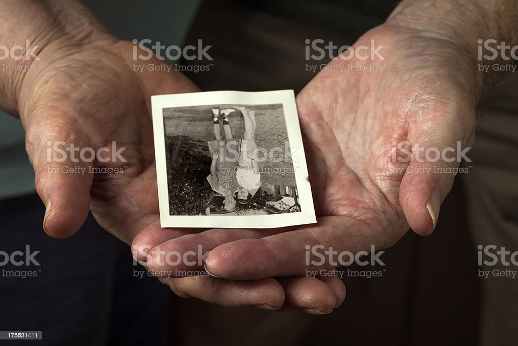 Closeup of Elderly Couple Hands Holding Old Honeymoon Photo stock photo