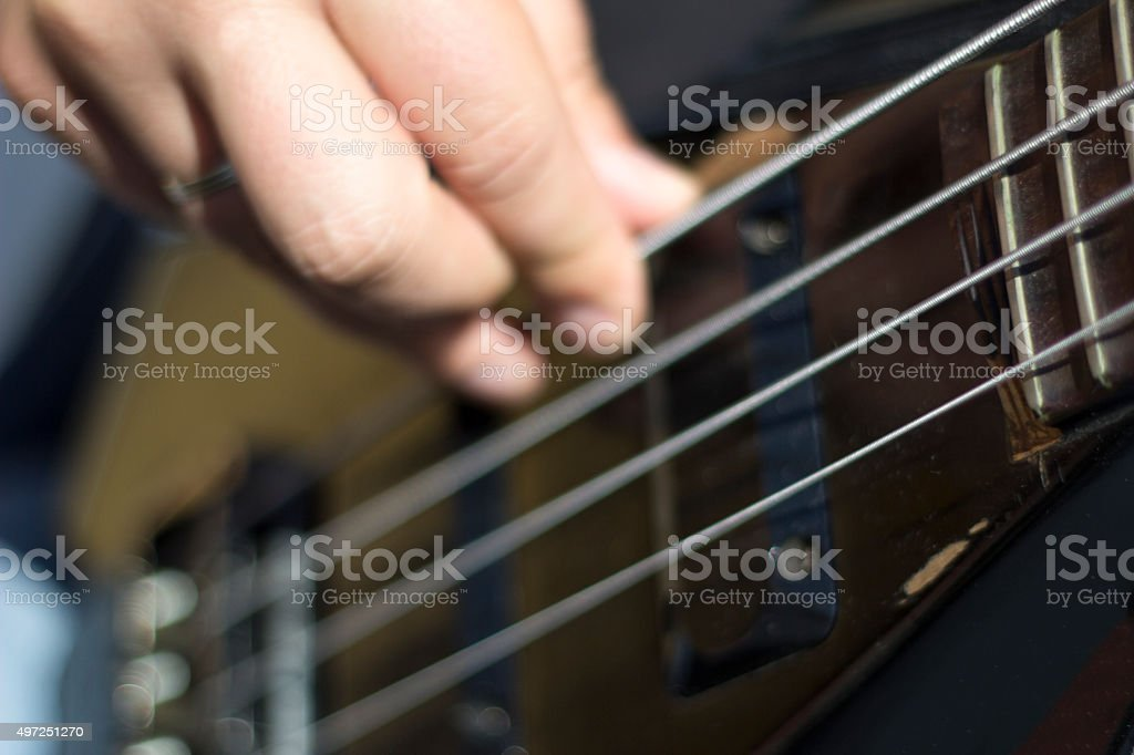 Closeup of electrical bass guitar strings with fingers on it stock photo