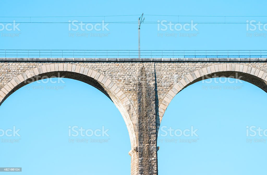 Close-up of elevated railway stone arch bridge on blue sky stock photo