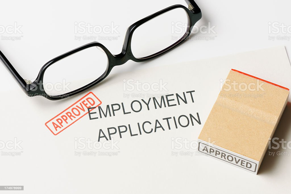 Close-up of employment application with 'Approved ' rubber stamp with glasses royalty-free stock photo