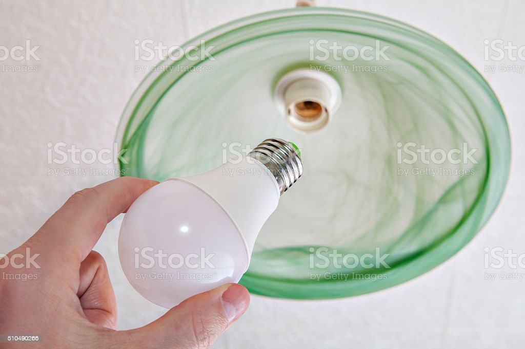 Close-up of energy-saving LED light bulb in human hand. stock photo