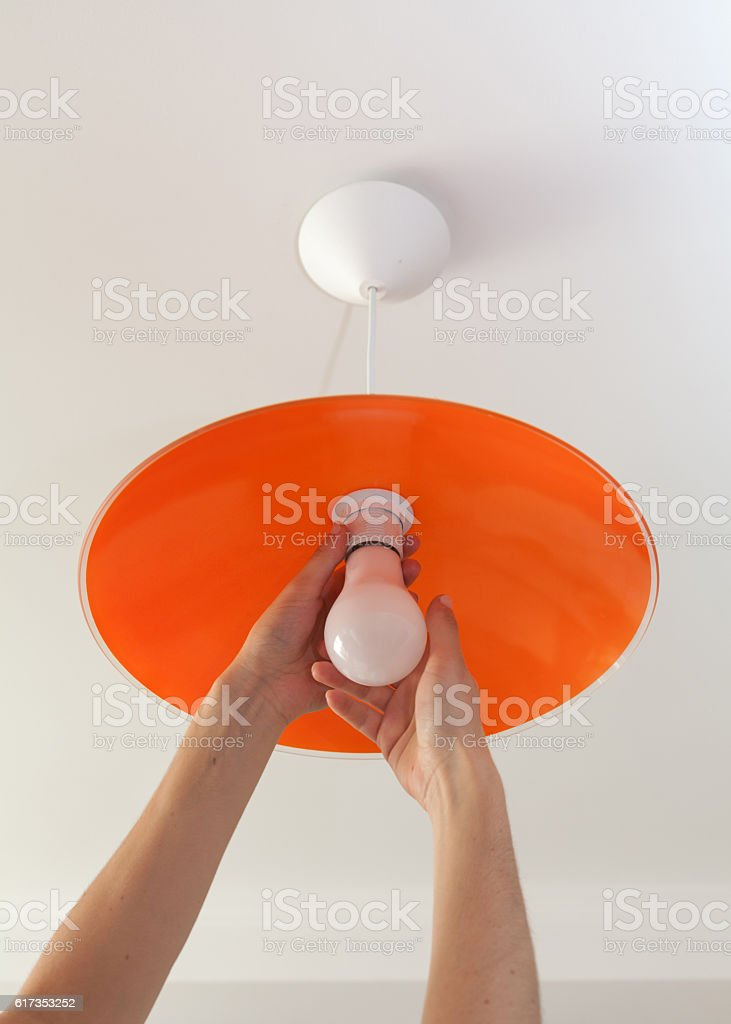 Close-up of energy-saving LED light bulb in the human hand stock photo