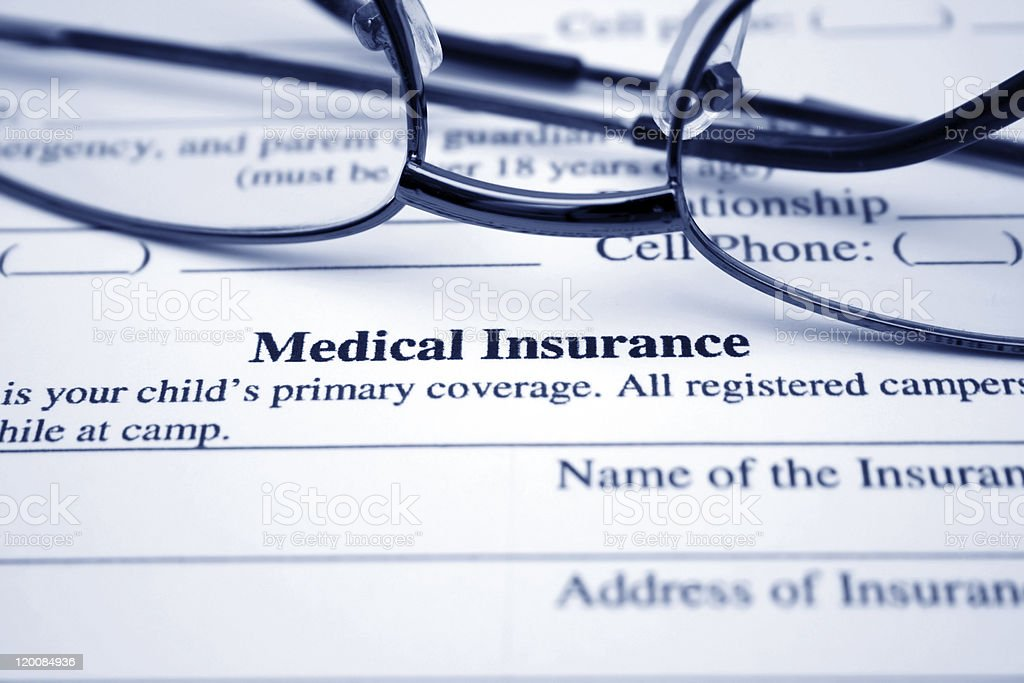 Close-up of eyeglasses on top of medical insurance brochure stock photo