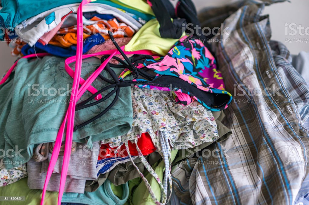 Close-up of fabric on a bunch of laundered ironing clothes. Shallow depth of focus. stock photo