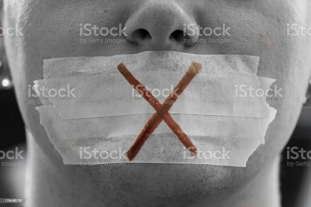 Close-up of face with tape over mouth and cross drawn on it stock photo