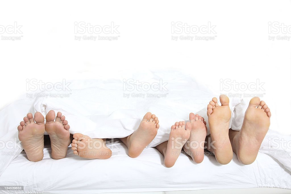 Closeup of family feet in bed stock photo