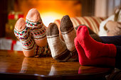 Closeup of family feet in wool socks at fireplace