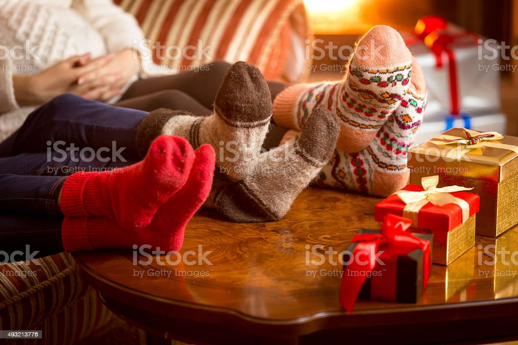 Closeup of family's legs in woolen socks next to fireplace stock photo