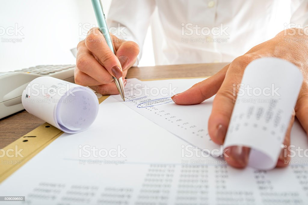 Closeup of female accountant looking through the receipts stock photo