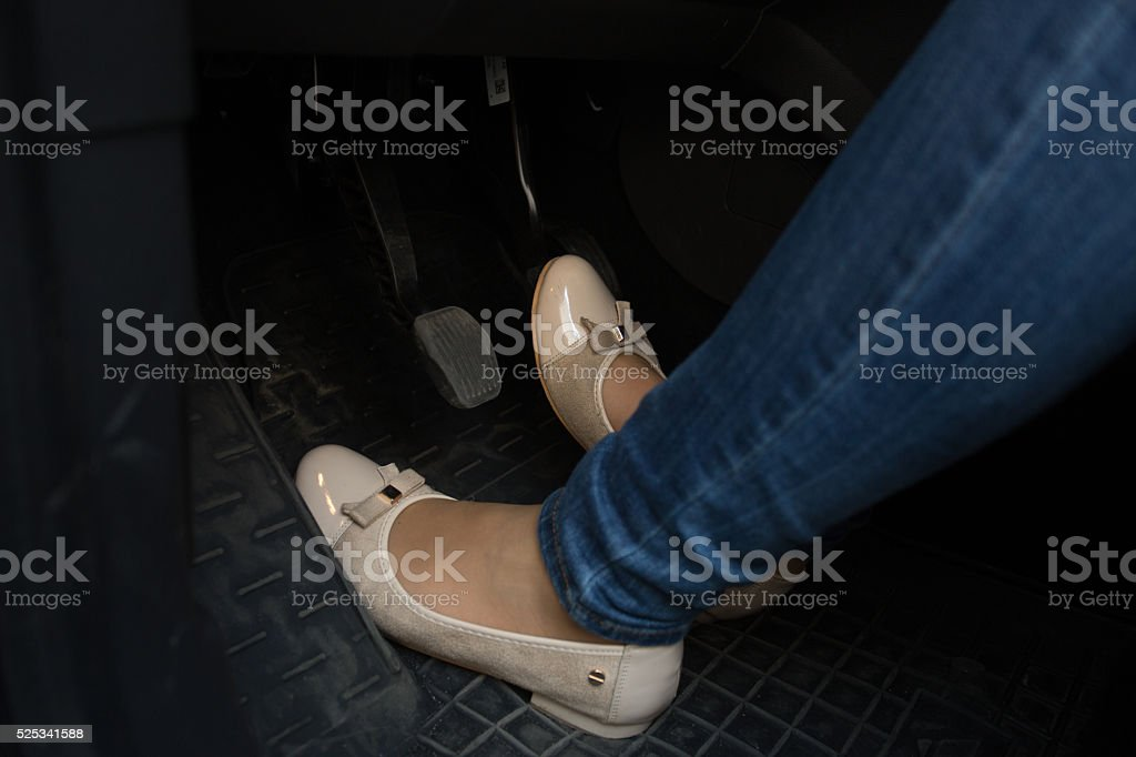 Closeup of female driver feet on car pedals stock photo