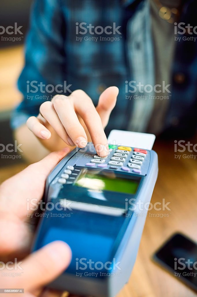 Close-up of female entering pin on card reader stock photo