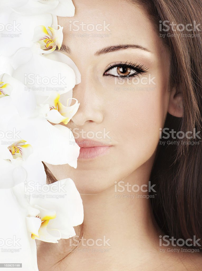 Close-up of female face half hidden by white flowers royalty-free stock photo