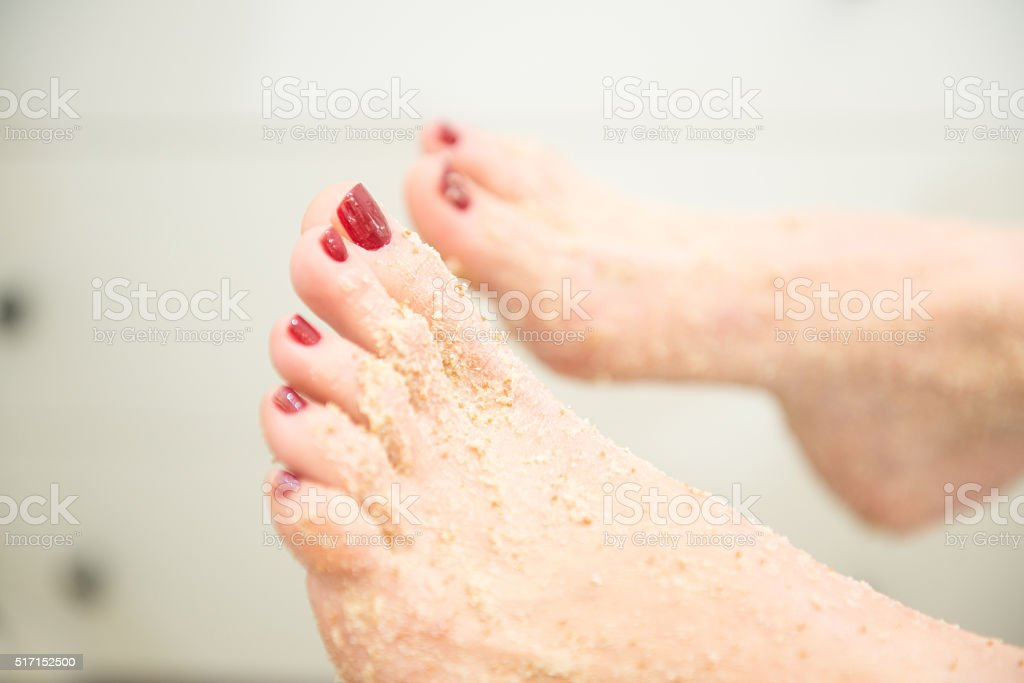 Close-up of Female Feet with Exfoliating Foot Scrub, Red Pedicure stock photo