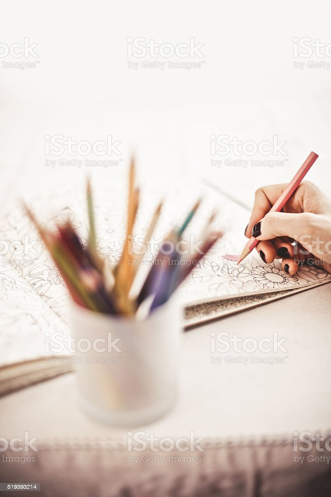 Close-up of female hand Coloring Book at Home stock photo