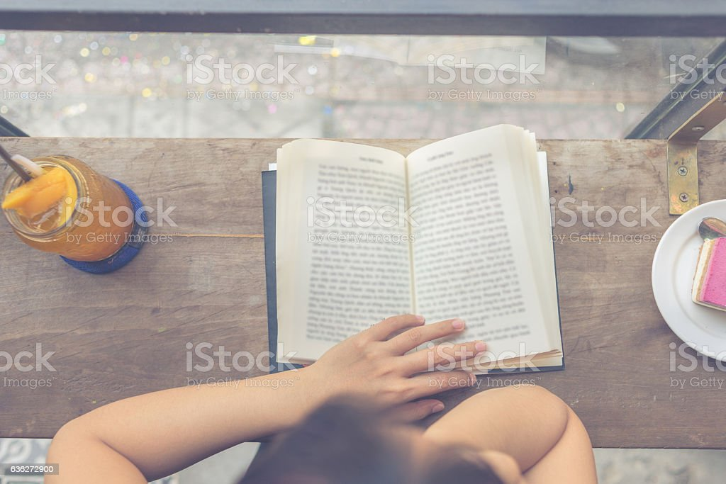 Close-up of female hand holding opened book on wooden table stock photo
