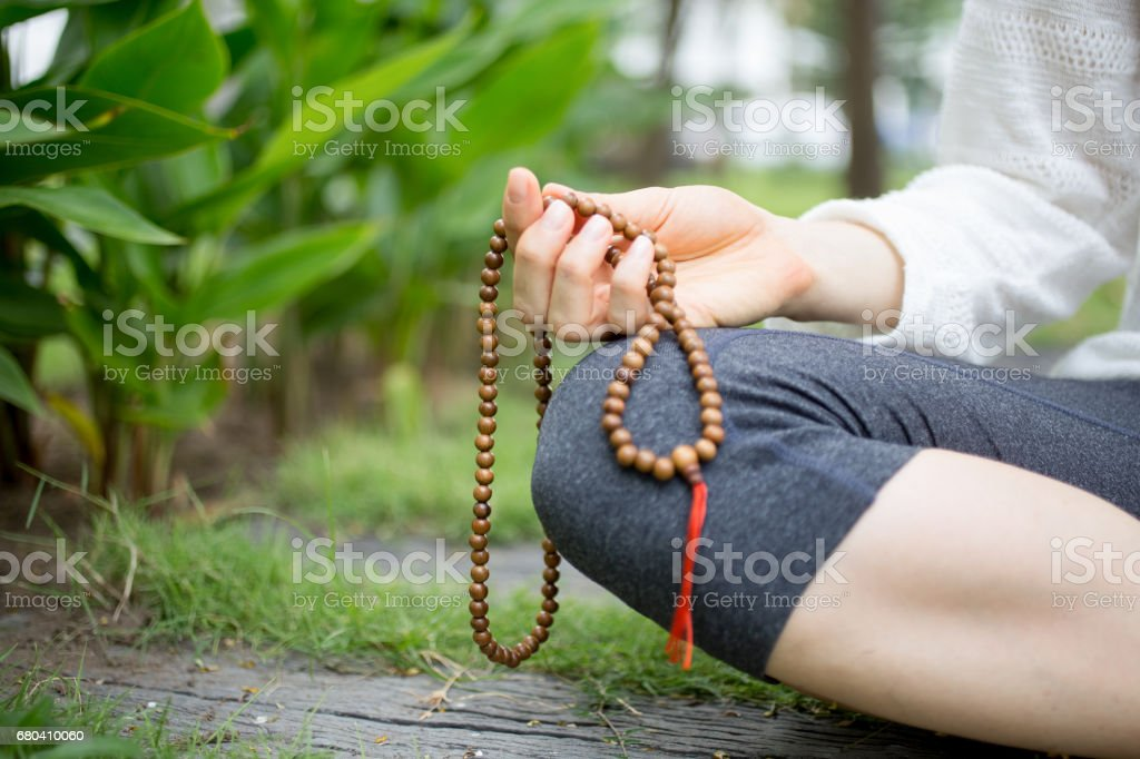 Close-up of female hand holding rosary beads stock photo