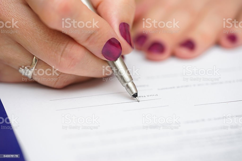closeup of female hand signing document stock photo