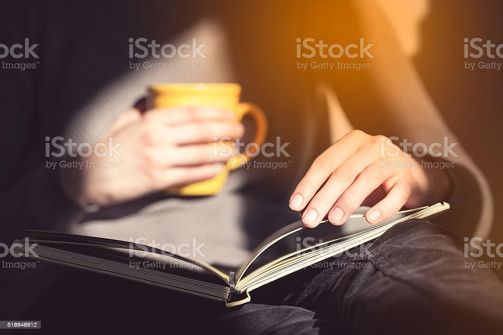 Close-up of female hands holding open book. Woman reading book. stock photo