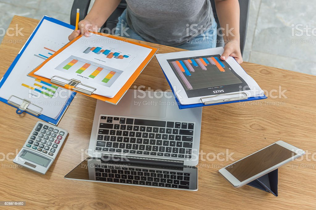 Close-up of female hands holding two sales report while analysing stock photo