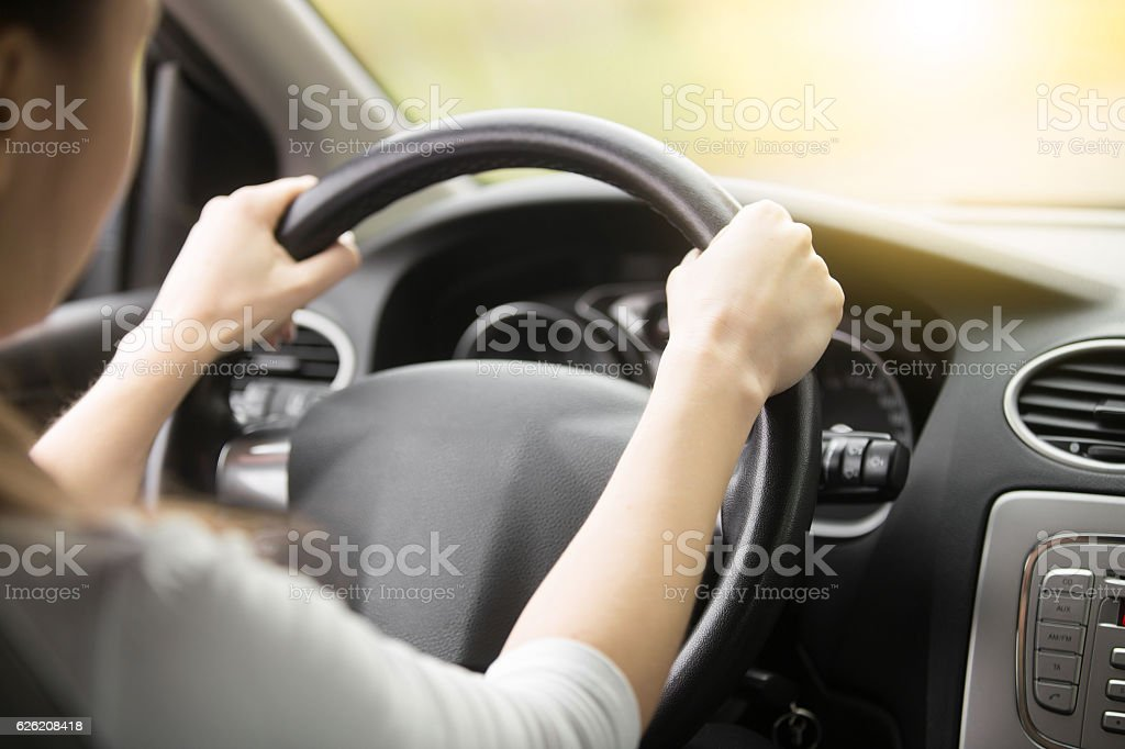 Close-up of female hands on the steering wheel stock photo