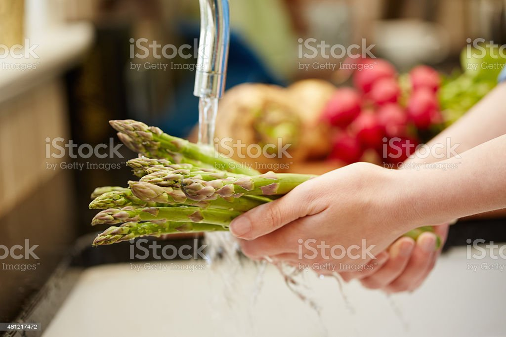 Close-up of female hands washing asparagus under faucet stock photo