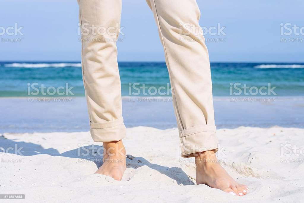 Close-up of female legs in pants barefoot on the beach stock photo