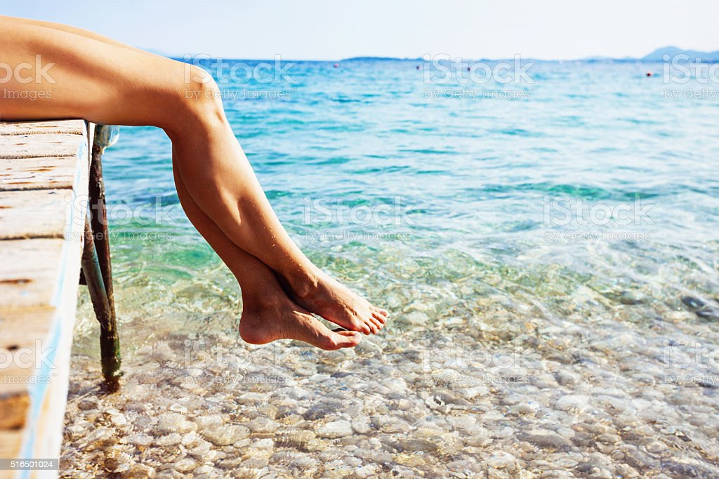 Closeup of female legs over the sea stock photo