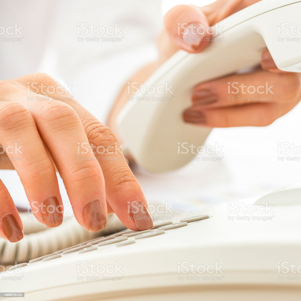Closeup of female telephone operator dialing a phone number stock photo