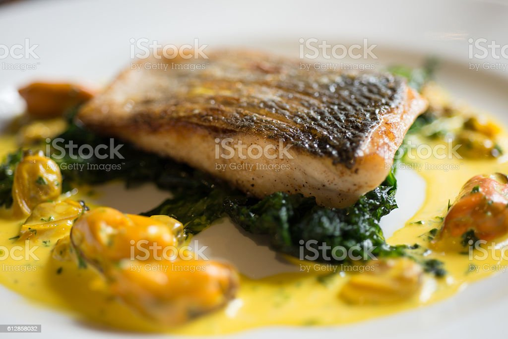 Closeup of Filleted Fish with Yellow Mussel Sauce stock photo