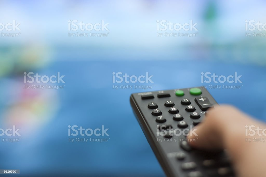 Close-up of fingers on the remote, changing the channel royalty-free stock photo