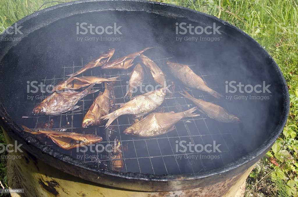 closeup of fish smoking for food in retro barrel royalty-free stock photo