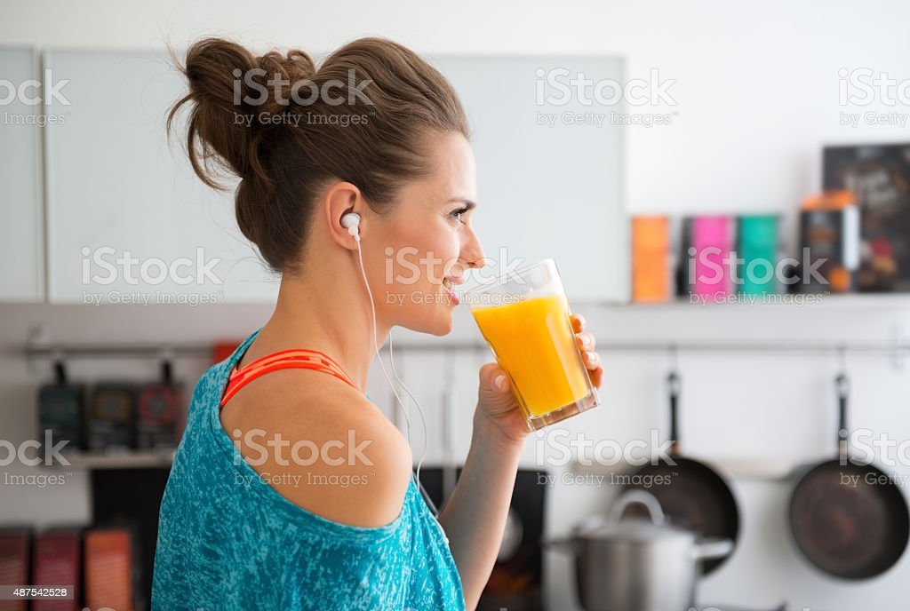 Closeup of fit woman in profile starting to drink smoothie stock photo