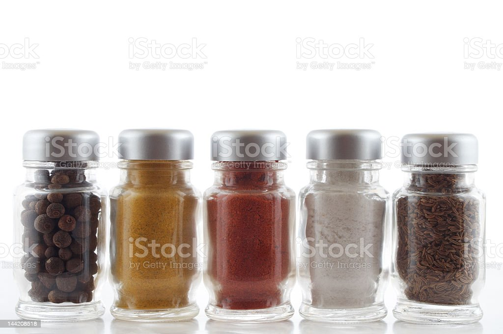 Close-up of five bottles of colorful spices stock photo