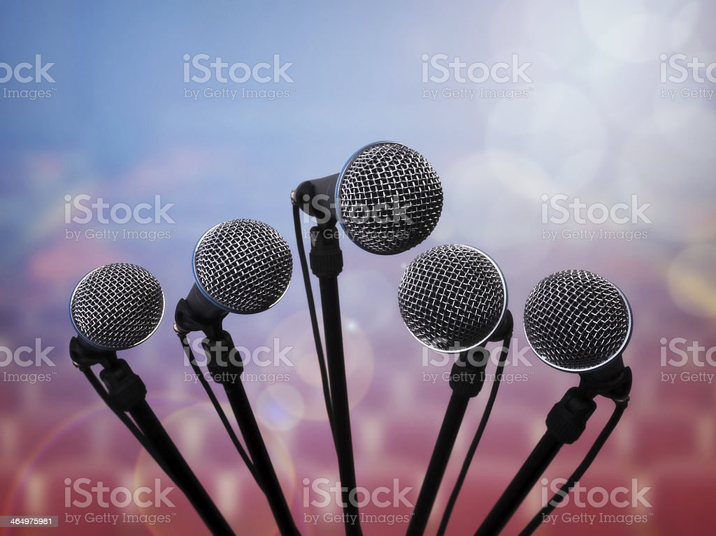 Close-up of five microphones on stands with an abstract back stock photo