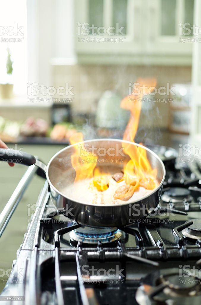 Close-up of flames rising from frying pan stock photo