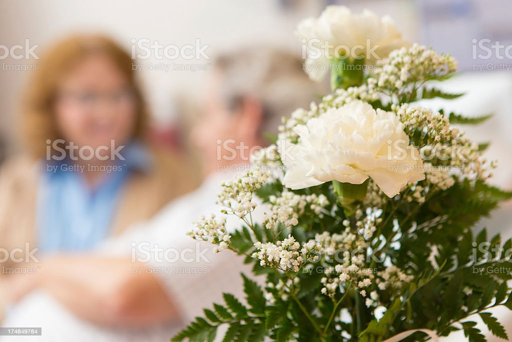 Closeup of flowers with senior couple in hospital patient room stock photo