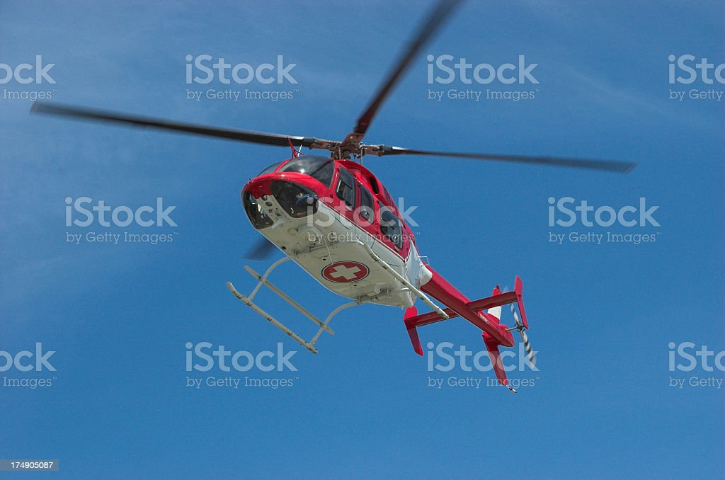 Closeup of flying red helicopter in contrast with blue sky stock photo