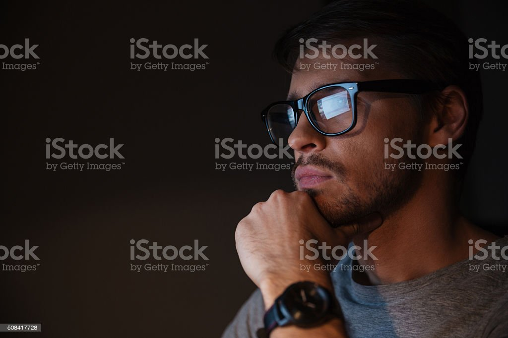 Closeup of focused man in glasses looking at screen stock photo