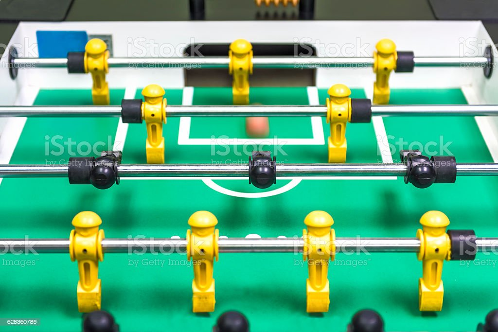 Closeup of foosball table with figures and ball rolling stock photo